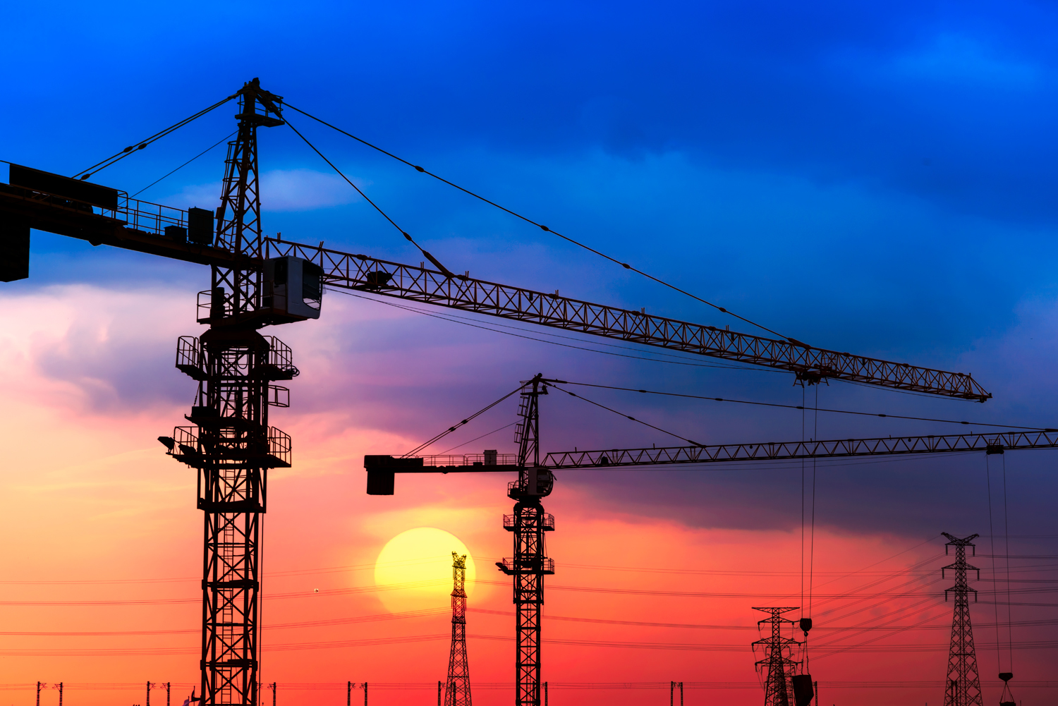 Industrial construction cranes and building silhouettes over sun